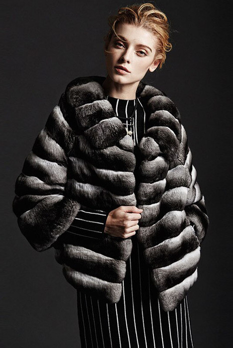 chinchilla fur coat waist length , round collar , cropped sleeves on model matched with black and white dress