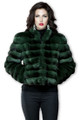green chinchilla coat on brunette model wearing black jeans and blouse , accessorized with pearl earrings
