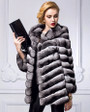 mid-hip length chinchilla fur coat with hood on model accessorized with black leather , minimalistic bag