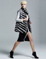 chinchila vest  on model  with black knee length slitted dress and black high heels
