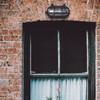 Ceduna Nautical Bulkhead Light in Black (AM-G526-BK) over a window on a brick wall
