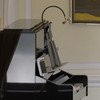 """Side angle of 22"""" Piano lamp mounted on a piano"""