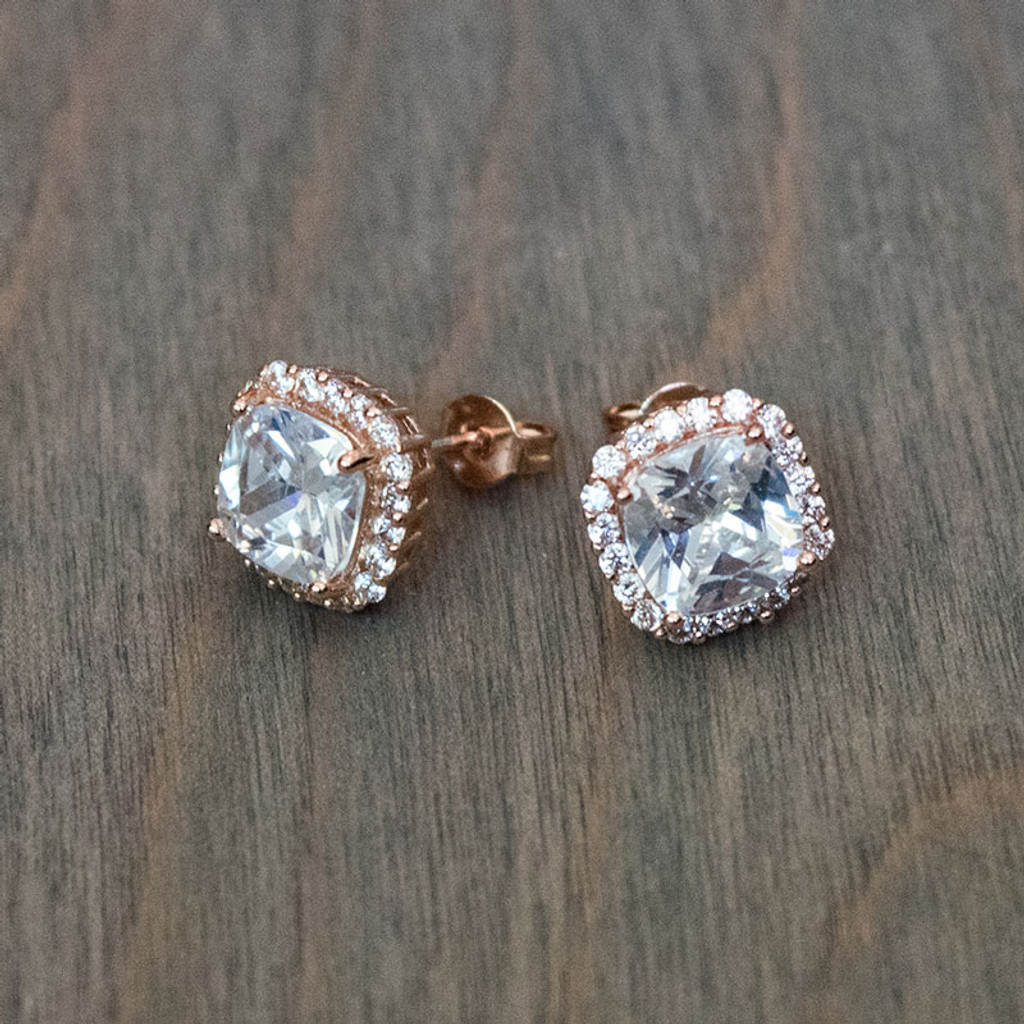 Rose Gold crystal earring studs are cushion cut Cubic Zirconia crystals surrounded in a halo of pave crystals. Each earring measures just under half an inch (3/8th an inch) long.