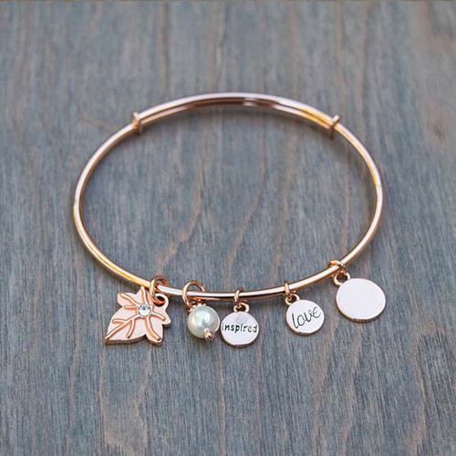 "Beverly's Rose Bangle Bracelet by Avalee's Glamour features an ivy leaf crystal charm, a pearl charm, and ""inspire"" and ""love"" rose gold charms."