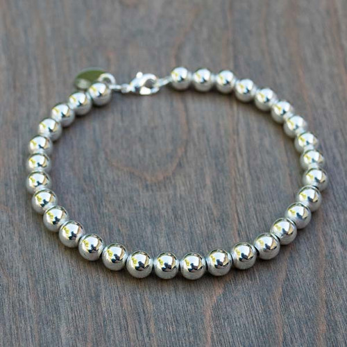 Bailey's Beads Bracelet is a 6mm silver plated beaded bracelet. It is the perfect bracelet for wearing on its own or with as many charms as desired.  It looks great stacked with other bracelets.