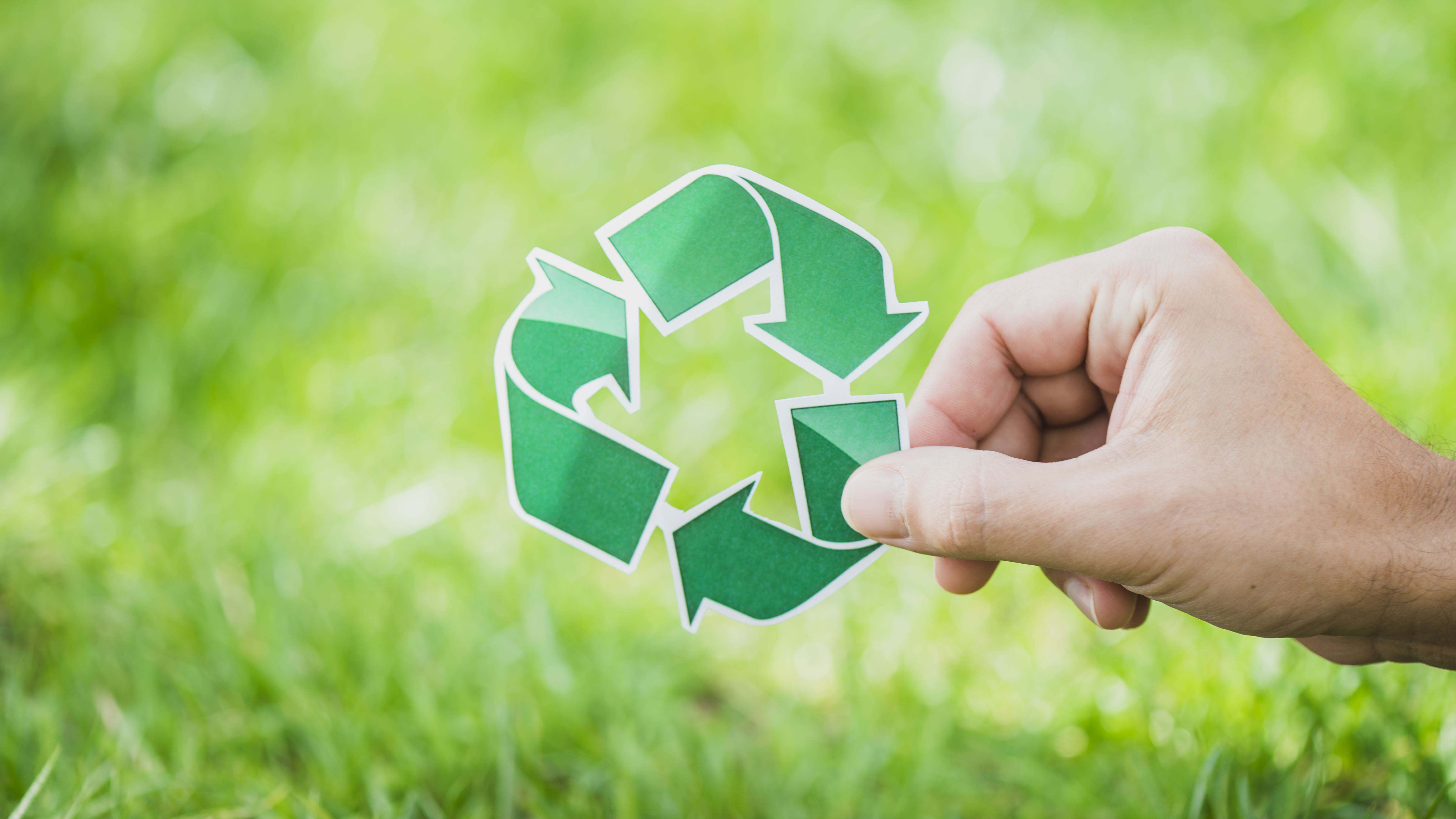 hand-holding-recycle-symbol-against-green-grass.jpg