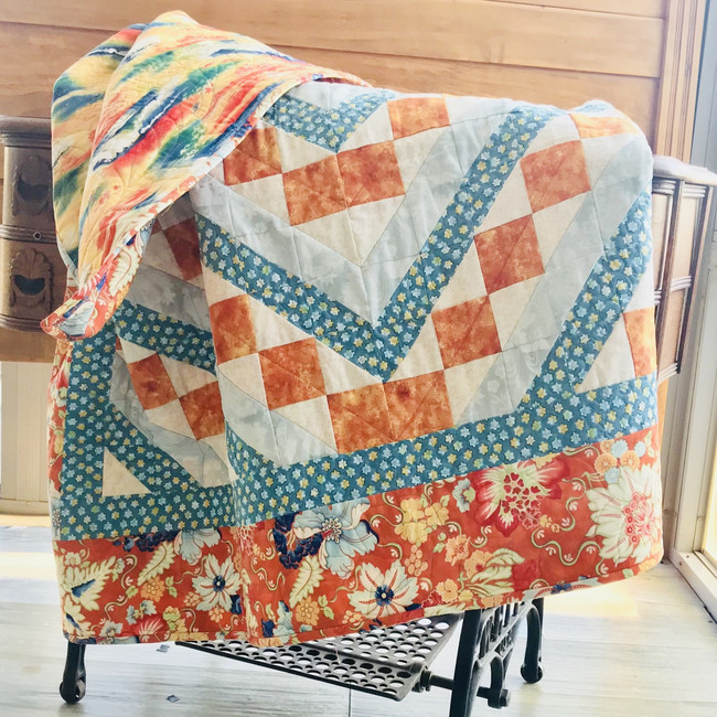 Orange squares form a diagonal pattern across the quilt. Highlighted with teal fabrics. Cotton fabric and cotton batting. Machine sewn