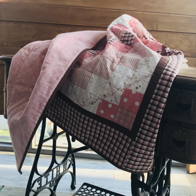 Pink and brown woven plaid squares form a fun pattern. Decorative stitches hold the layers together. Cotton fabric and cotton batting. Machine sewn.