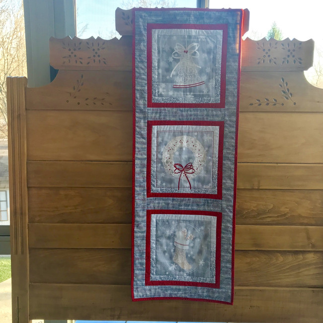 Three holiday panels (a bell, wreath, and stocking) are sewn together to make a cute holiday decoration. Cotton fabric and cotton batting. Machine sewn.