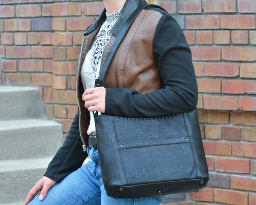 Short strap for over the shoulder carry and concealed pocket access left and right