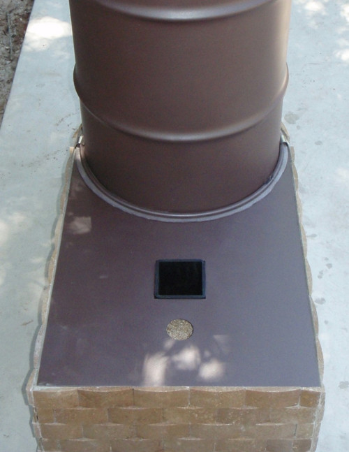 "This is a 4"" Rocket Heater style with tile attached to the outside. Wood is fed through the square hole; the small round hole accommodates some extra air for the burn."