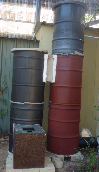 """Derrick prototype. The stack containing the heat riser is 2 barrels tall. The adjacent bell is 3 barrels tall or 102"""". Fireclay bricks are stacked inside all the way up the 3 steel drums. Derrick can be built with 2, 2½, or 3 barrels in the bell tower. The higher the bell tower, the more fireclay bricks for greater heat storage capacity. It would also be possible to make a second bell vertically from steel drums or horizontally as a bench."""