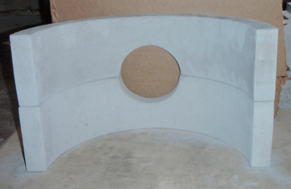 """Here you can see the 2 partial circle firebricks dry fitted together. They are the same radius as a 30 gallon metal barrel. The hole fits any piece of single wall 6"""" stove pipe. In our pictures, we are using a 90° elbow to connect to a vertical chimney."""