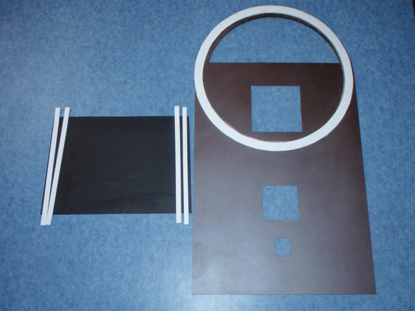 Here is a top plate painted bark brown metallic and a divider plate painted black. The round white gasket fits underneath a 30 gallon barrel; it prevents the exhaust gases from escaping into the room. Gaskets on both sides of the divider plate also divide the exhaust gases from the incoming air for combustion around the burn tunnel.
