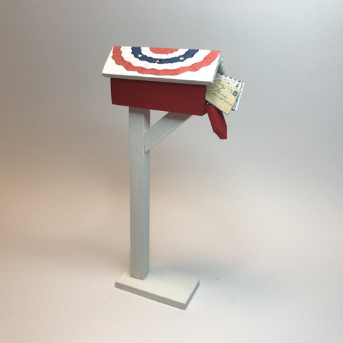 Red mailbox with patriotic bunting covered roof (shown open)