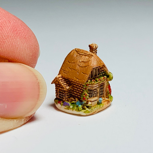 Tiny Cottage Sculpture (FCA4325) shown with fingers for scale