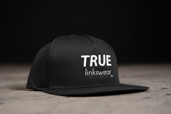 Snap-back black TRUE logo hat side view