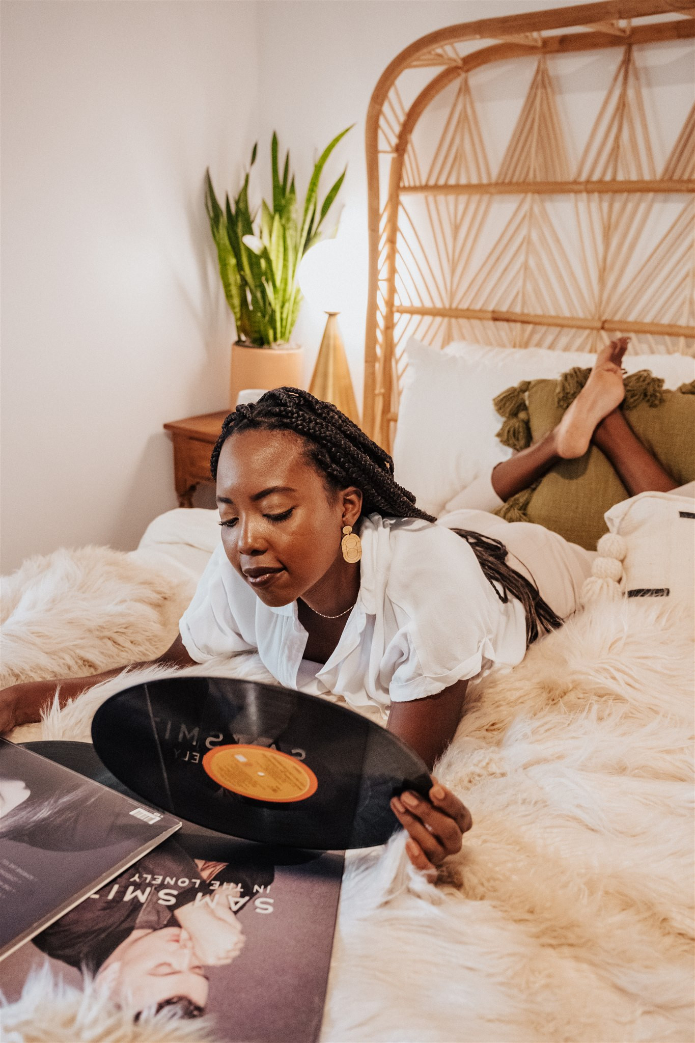 women with vinyl on a bed with dangle earrings