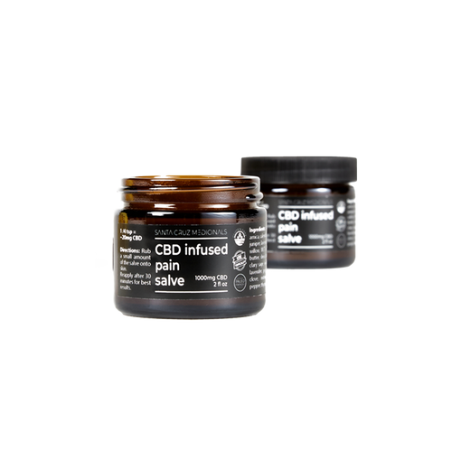 """Two dark brown glass jars with black lids, the one in the forefront is open. A black label with white letters reads """"CBD infused pain salve"""""""