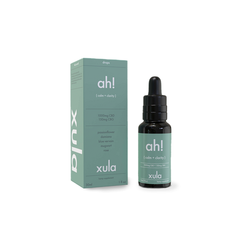xula's ah! calm + clarity tincture, next to its packaging. The tincture is in a dark glass bottle and the label and the package are both a robin's egg blue.