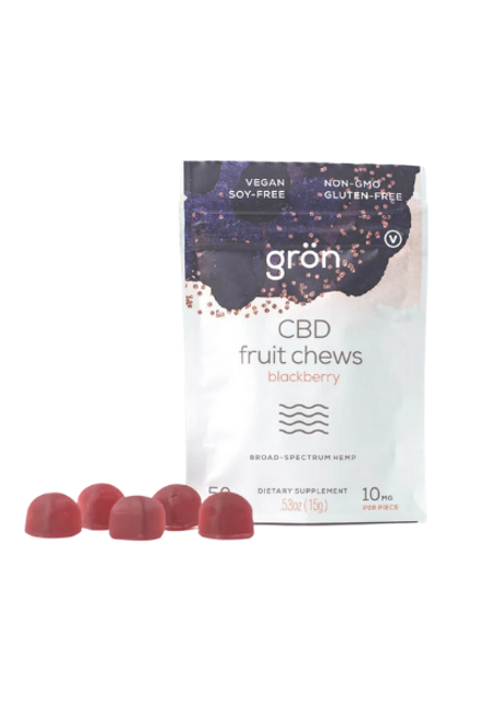 Grons fruit chews with a few blackberry chews to the left of the package which is dark blue and white packaging with CBD fruit chews on the front.