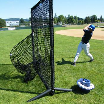 Young baseball player hitting balls into a sock net
