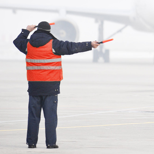 Airport ground services worker wearing ewool® PRO heated vest under his coat