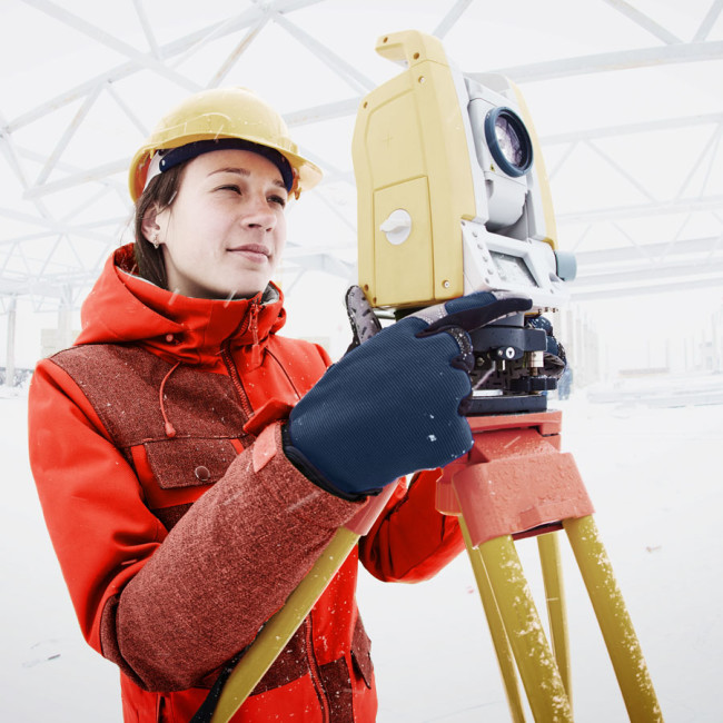 Land surveyor wearing ewool® PRO heated vest under her coat