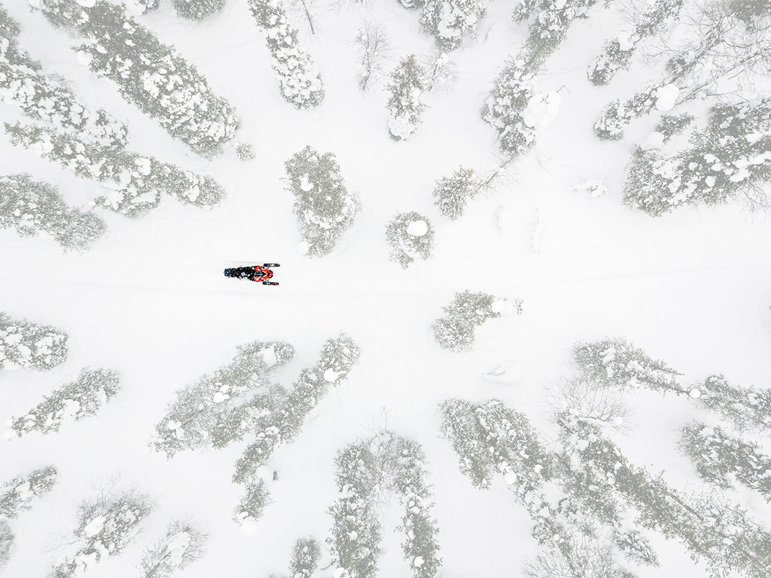 Snowmobiler wearing a heated vest traversing the forest