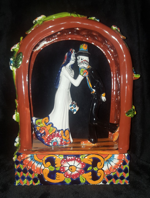 Day of Dead Bride and Groom under Arch covered in flowers. Front view