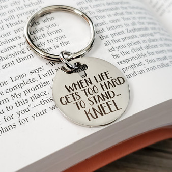 Kneel and Pray Quote Silver Key Chain on open bible