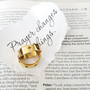 gold cross ring on paper that says prayer changes things