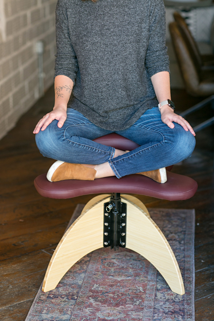 Woman sitting cross-legged on Soul Seat Bamboo in Natural and Merlot