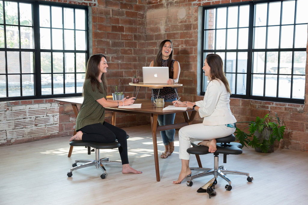Flow Desk, Tria used as standing desk with women sitting on Soul Seat chairs