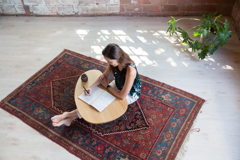 Woman writing at Floor Desk, Tria with legs outstretched