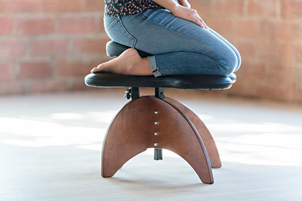 Woman sitting on Soul Seat with wooden legs in kneeling position