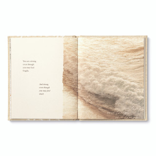 """Inside pages, """"Even Though"""", an encouragement book with a calming, neutral cloth cover design, written by M.H. Clark, inside page copy """"You are strong, even though you may feel fragile. And strong even though you may feel stuck."""" and includes an image of the ocean current along the shoreline"""