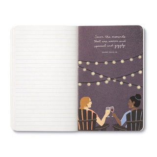 """Inside page, wine-themed journal with 8 breakout pages, each featuring a uniquely designed, vibrant illustration and sweet quote, celebrating life's simple pleasures and the people we share them with. This illustration features two woman sitting under outdoor night lights, toasting wine glasses, quote featured """"Savor the moments that are warm and special and giggly."""" -Sammy Davis Jr."""