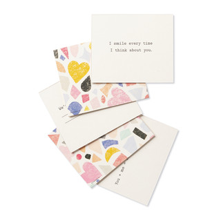 """Multi-card view, a playful set of compliment cards for someone special, bright and colorful sleeved box, features elegant gold foil stamping, includes 20 cards, each with a unique messages. Message on this card is """"I smile every time I think about you"""""""