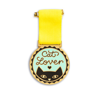 """An award medal with a yellow ribbon and an illustration that reads """"Cat Lover."""""""
