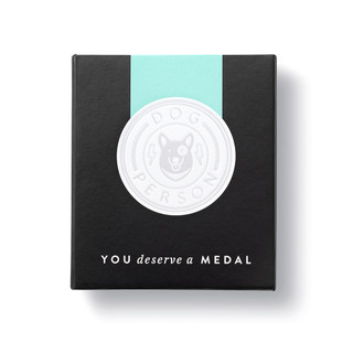 """Front box view, an award medal with a teal blue ribbon and an illustration that reads """"Dog Person"""", includes keepsake gift box, black slip cover with medal image in cover, medal sits securely in tray box"""