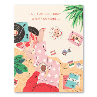 """Card front, cream colored birthday card with colorful illustrations of a woman indulging in self-care by  listening to music on a record player, with Polaroid pictures of friends scattered around her. The statement reads """"For your birthday, I wish you more..."""""""