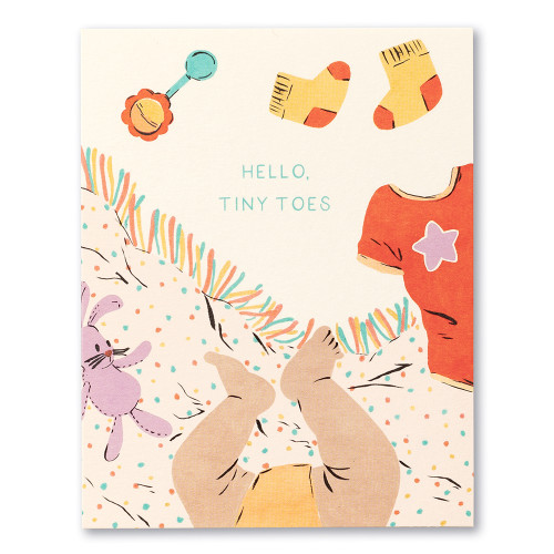 """Card front, cream colored baby card featuring colorful illustrations of cute baby feet and scattered toys. The statement on the front of the card reads """"Hello, tiny toes."""""""
