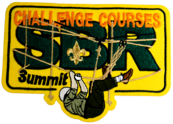 "rectangular yellow patch with dark green letters ""SBR"" covered by orange letters ""challenge courses"". On the bottom of the patch, a person climbing horizontally across ropes."