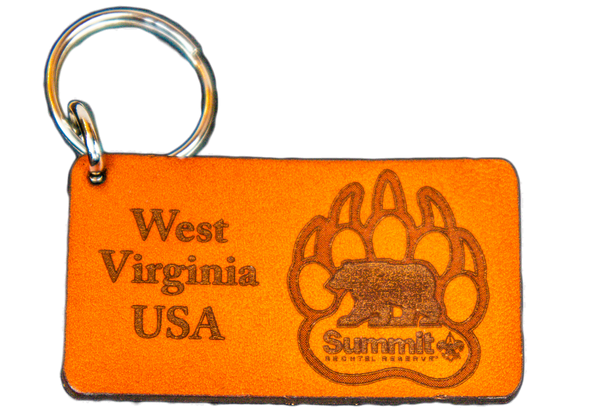 "Rectangular light brown leather cutout on a keychain, with ""West Virginia USA"" on left and bear/paw logo on right"