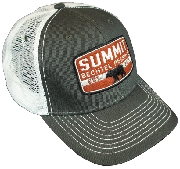 Trucker Cap with white mesh back and dark gray front.  A rust orange colored patch front center that says, Summit Bechtel Reserve, has a black bear in the center of the patch with the establish date of 2013 and has a plastic snap closure. -Side View