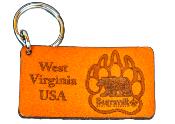 """Rectangular light brown leather cutout on a keychain, with """"West Virginia USA"""" on left and bear/paw logo on right"""