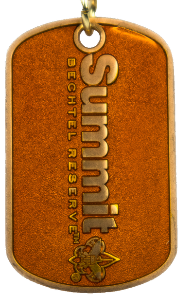 vertical view of dog tag with orange interior and brass outline. Raised in the center is a brass Summit logo. The tag is connected to a gold chain.