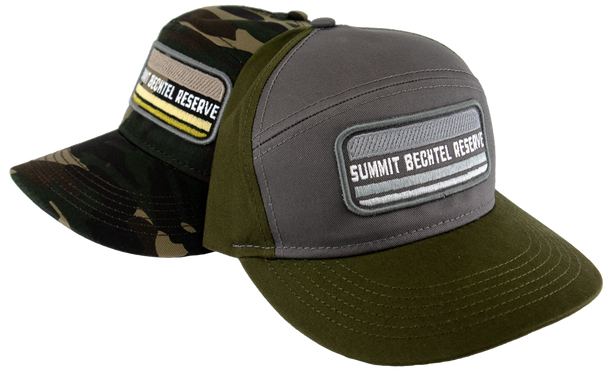 High profile cotton cap with a seamless front panel with a center patch that says, Summit Bechtel Reserve and has a plastic snap closure.  Two colors pictured, left cap is camo and cap on the right is loden green back and bill and a gray front panel.
