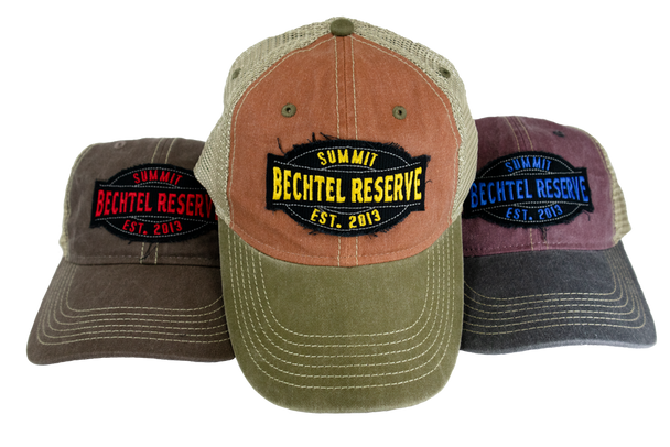Weathered look Trucker Cap with front patch that says, Summit Bechtel Reserve, Established 2013 and has a plastic snap closure. Pictured left to right are Coffee/Khaki, Rust/Khaki, Henna/Khaki.